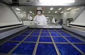An employee dries newly made solar panels at a factory of a photovoltaic company in Jiaxing, Zhejiang province June 5, 2013.  REUTERS/William Hong