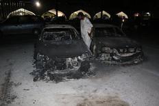 Сожженные машины в аэропорту Триполи, 14 июля 2014 года. Боевики обстреляли в понедельник аэропорт Триполи, уничтожив большую часть находившихся там самолетов. Ожесточенные бои между военизированными отрядами заставили ООН вывести своих сотрудников из североафриканской страны. REUTERS/Hani Amara