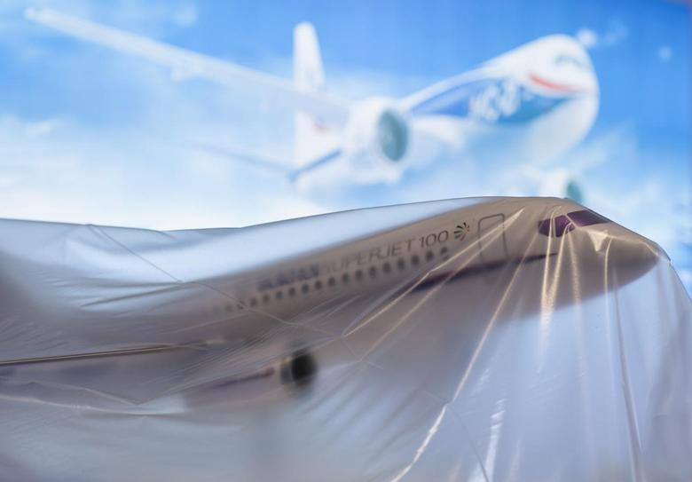 A Russian Sukhoi Superjet SSJ-100 model aircraft sits under plastic sheeting at the 2014 Farnborough Airshow in Farnborough, southern England July 13, 2014. REUTERS/Kieran Doherty