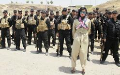 Kurdish pop star Helly Luv poses in front of Kurdish Peshmerga troops at a base in Dohuk in this July 5, 2014 picture provided by Kawin Cihad Tahlavi and made available to Reuters on July 8, 2014. REUTERS/Kawin Cihad Tahlavi/Handout via Reuters