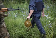 Сапер с миной в украинском поселке Семеновка, 14 июня 2014 года. Россия пригласила военных атташе 18 стран, включая США, посетить во вторник город в Ростовской области, где, по её утверждению, упал прилетевший с Украины снаряд, унеся человеческую жизнь. REUTERS/Gleb Garanich