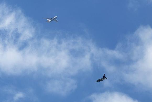 The Eurofighter Typhoon performs a manoeuvre as a passenger plane flies above during its display at the 2014 Farnborough International Airshow in Farnborough, southern England July 14, 2014. REUTERS/Kieran Doherty