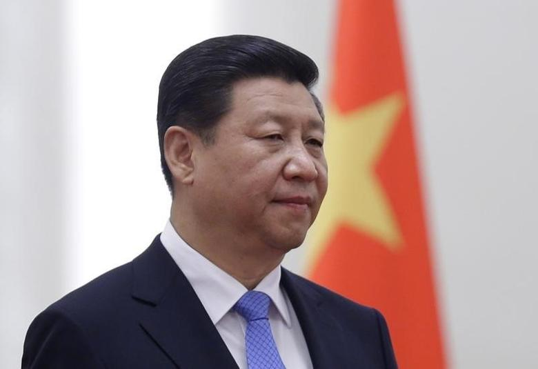 China's President Xi Jinping stands next to a Chinese national flag during a welcoming ceremony at the Great Hall of the People, in Beijing, November 13, 2013. REUTERS/Jason Lee