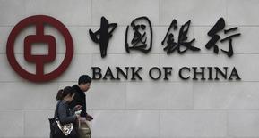"""En la imagen, dos personas pasan delante de un logo de del Banco de China en su sucursal en Pekín el 26 de marzo de 2013. China mantendrá su política monetaria """"prudente"""" en la segunda mitad del año, dijo un funcionario de alto rango del banco central del país citado el martes por la radio estatal. REUTERS/Kim Kyung-Hoon"""