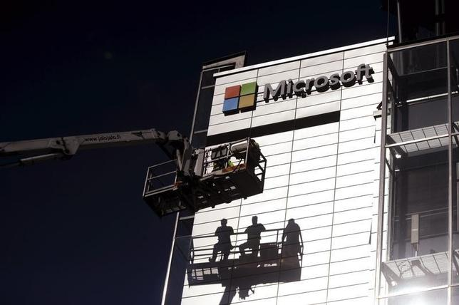 Workers install the logo of U.S. technology giant Microsoft on the wall of Nokia's former headquarters in Espoo April 26, 2014. REUTERS/Mikko Stig/Lehtikuva