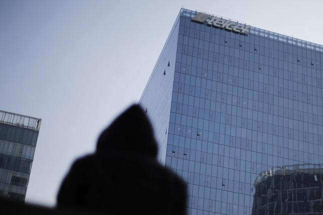 A man stands in front of the headquarters of Carlos Slim's mobile phone company Telcel, commercial brand of America Movil, in Mexico City July 9, 2014.  REUTERS/Bernardo Montoya