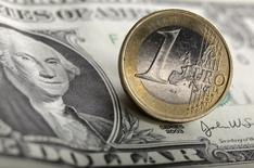 Банкнота в 1 доллар и монета 1 евро, Варшава, 18 января 2011 года. Курс доллара растет после сообщения главы ФРС о возможности раннего повышения процентных ставок в случае быстрого роста занятости, а фунт стерлингов поднялся до шестилетнего максимума благодаря сильной инфляции. REUTERS/Kacper Pempel