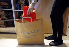 A sales assistant packs clothes at a Primark store on Oxford Street in London June 20, 2014. REUTERS/Luke MacGregor