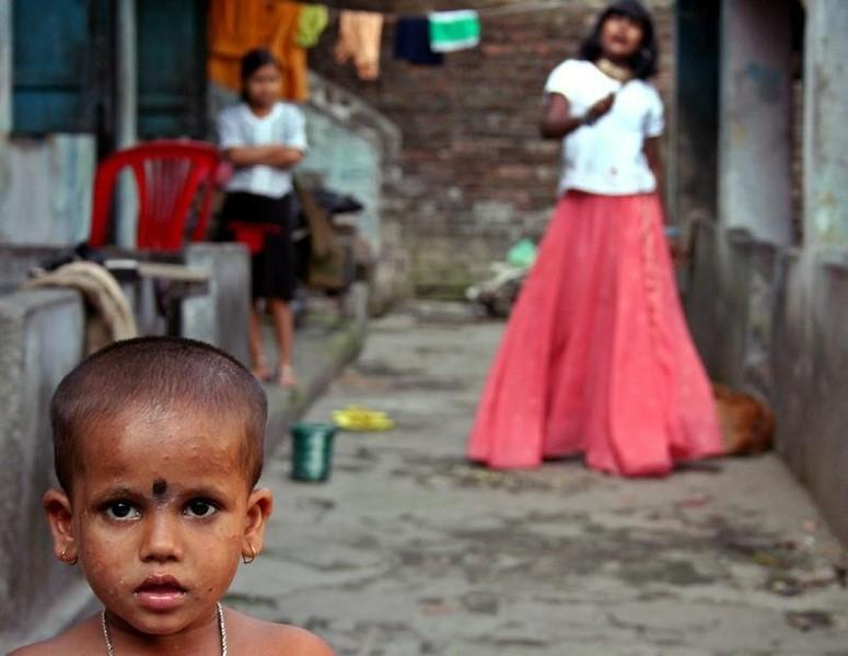 Piya Das (L), a five-year-old HIV-positive patient, stands outside her house in Siliguri December 1, 2005. REUTERS/Files