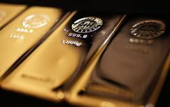 Золотые слитки в магазине Ginza Tanaka в Токио 18 апреля 2013 года. Цены на золото растут после двухдневного спада, но по-прежнему близки к минимуму четырех недель за счет укрепления доллара и вероятности раннего повышения процентных ставок ФРС. REUTERS/Yuya Shino