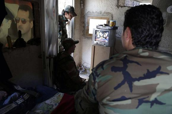 Soldiers loyal to Syria's President Bashar al-Assad sit as they watch TV broadcasting Al-Assad speaking as he is sworn in for a new seven-year term, in a checkpoint in Damascus July 16, 2014. REUTERS/Omar Sanadiki