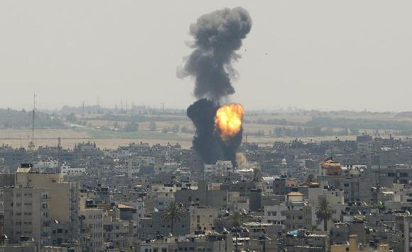 Smoke and flames are seen following what witnesses said was an Israeli air strike in Gaza City July 16, 2014. REUTERS/Ahmed Zakot