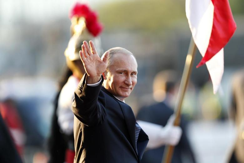 Russia's President Vladimir Putin waves as he leaves the Itamaraty Palce after the 6th BRICS summit and the Union of South American Nations (UNASUR), in Brasilia July 16, 2014. REUTERS/Ueslei Marcelino
