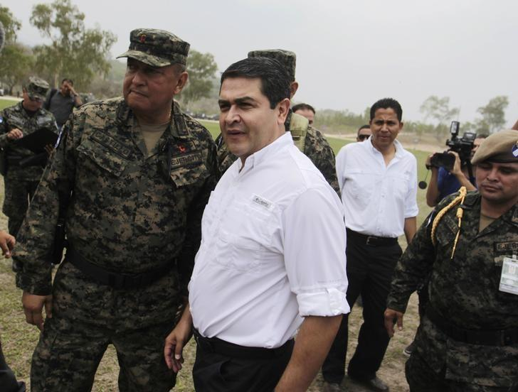 Honduras' President Juan Orlando Hernandez (C) talks to officers of Honduras' army during a presentation in Mateo, on the outskirts of Tegucigalpa May 7, 2014 file photo. REUTERS/Jorge Cabrera
