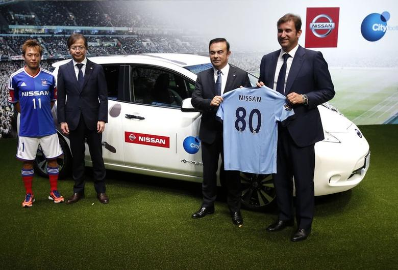 Nissan Motor Co's President and Chief Executive Officer Carlos Ghosn (2nd R) holds a Manchester City jersey with Manchester City Football Club Chief Executive Officer Ferran Soriano (R) as they pose with President of Japan's football club Yokohama F. Marinos Akira Kaetsu (2nd L) and player Manabu Saito (L) after a joint news conference in Yokohama, south of Tokyo July 17, 2014. REUTERS/Yuya Shino