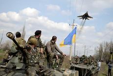Украинские военные на бронемашинах в Краматорске 16 апреля 2014 года. Украина сообщила о потере ещё одного военного самолёта на востоке, где её войска ведут бои с пророссийскими сепаратистами, и назвала это делом рук российских ВВС - обвинение, которое Минобороны России не смогло прокомментировать в четверг. REUTERS/Maks Levin