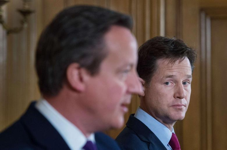 Britain's Deputy Prime Minister Nick Clegg (R) listens to Prime Minister David Cameron speak at a joint news conference at 10 Downing Street in central London July 10, 2014.   REUTERS/Stefan Rousseau/Pool
