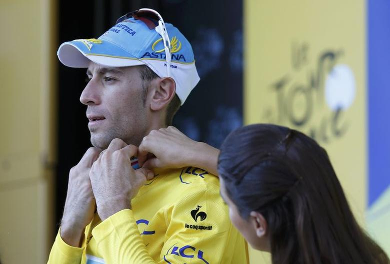 Astana team rider Vincenzo Nibali adjusts his leader's yellow jersey on the podium of the 185.5-km 12th stage of the Tour de France cycling race between Bourg-en-Bresse and Saint-Etienne July 17, 2014.       REUTERS/Jean-Paul Pelissier