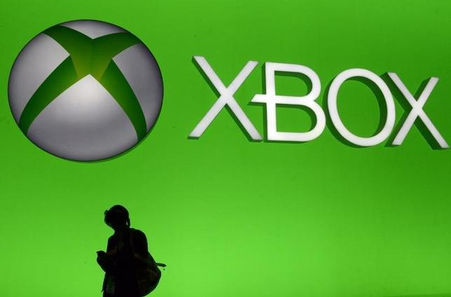 An attendee uses her smartphone in front of a giant Microsoft Xbox sign at the 2014 Electronic Entertainment Expo, known as E3, in Los Angeles, California June 11, 2014.  REUTERS/Kevork Djansezian