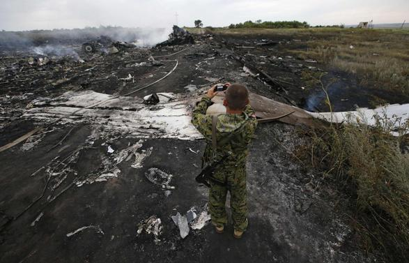 An armed pro-Russian separatist takes pictures at the site of a Malaysia Airlines Boeing 777 plane crash near the settlement of Grabovo in the Donetsk region, July 17, 2014.  REUTERS/Maxim Zmeyev