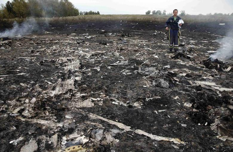 An Emergencies Ministry member walks at the site of a Malaysia Airlines Boeing 777 plane crash near the settlement of Grabovo in the Donetsk region, July 17, 2014. REUTERS/Maxim Zmeyev