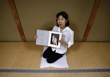 Misa Morimoto, the 50-year-old identical younger twin of Miho Yamamoto, shows a photograph of Miho and herself wearing traditional Japanese clothes known as Kimono taken to celebrate their 20th birthdays in 1984, during an interview with Reuters in Otsuki city, Yamanashi prefecture, July 15, 2014. REUTERS/Yuya Shino