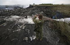 Um separatista pró-Rússia armado tira foto do local onde o avião da Malaysia Airlines caiu, na região de Donetsk, na Ucrânia, nesta quinta-feira. 17/07/2014 REUTERS/Maxim Zmeyev