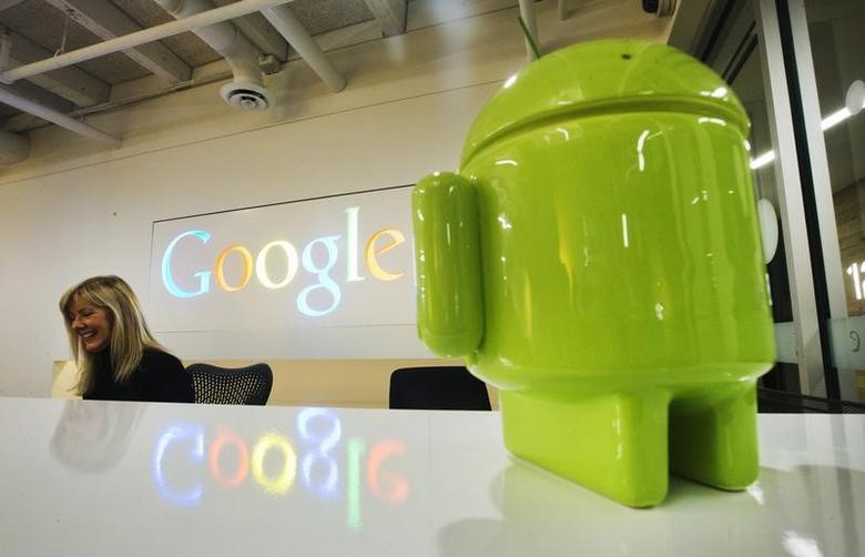 A Google Android figurine sits on the welcome desk as employee Tracy McNeilly smiles at the new Google office in Toronto, November 13, 2012. REUTERS/Mark Blinch/Fiiles