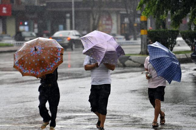 People hold umbrellas as they walk against rain in Qionghai, Hainan province, July 18, 2014.REUTERS/China Daily