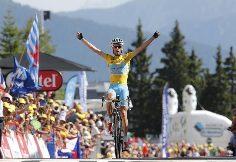 Race leader yellow jersey holder Astana team rider Vincenzo Nibali of Italy celebrates as he crosses the finish line to win the 197.5km 13th stage of the Tour de France cycling race between Saint-Etienne and Chamrousse, July 18, 2014.    REUTERS/Jean-Paul Pelissier