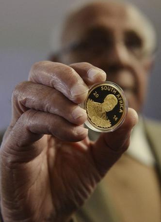 Former political prisoner Ahmed Kathrada holds a 24-carat gold coin honouring former president Nelson Mandela at the South African Reserve Bank in Pretoria, July 18, 2014. REUTERS/Stringer