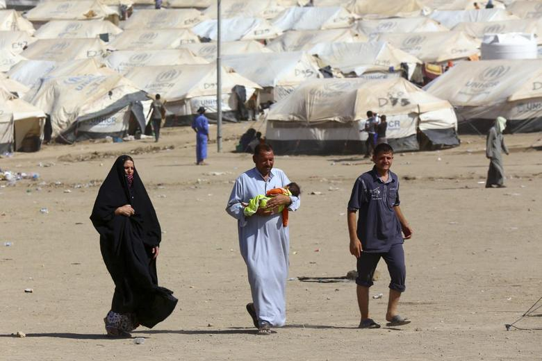 People who fled from the violence in Mosul walk inside the Khazer refugee camp on the outskirts of the Kurdish city of Arbil, July 17, 2014. REUTERS/Stringer