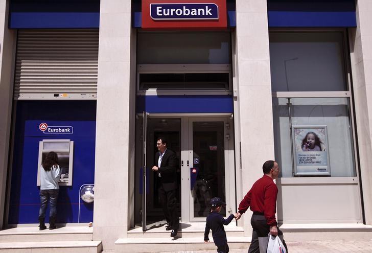 A man exits a Eurobank branch as a woman (L) makes a transaction at the branch's ATM  in Athens April 24, 2014.  REUTERS/Alkis Konstantinidis