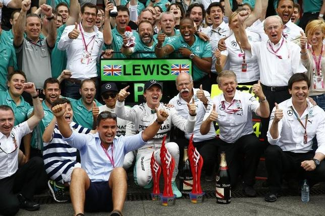 Mercedes Formula One driver Nico Rosberg of Germany ( front C) his team mate Lewis Hamilton of Britain (centre L) and Daimler CEO Dieter Zetsche (centre R) pose with the members of the Mercedes team after winning the German F1 Grand Prix at the Hockenheim racing circuit July 20, 2014. REUTERS/Michael Dalder