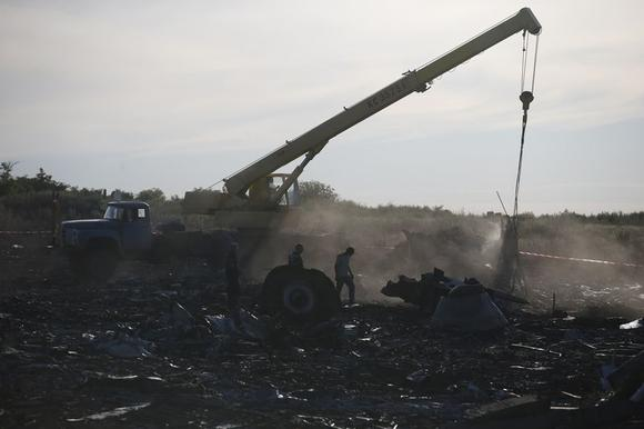 Members of the Ukrainian Emergencies Ministry and a crane operator work at the crash site of Malaysia Airlines Flight MH17, near the village of Hrabove, Donetsk region, July 20, 2014. REUTERS/Maxim Zmeyev