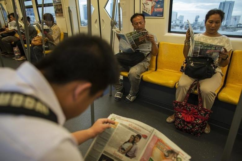 Passengers read the newspaper during rush hour on a skytrain in Bangkok July 8, 2013. REUTERS/Athit Perewongmetha