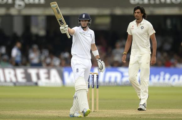 England's Joe Root waves his bat after reaching his half century as India's Ishant Sharma looks on during the second cricket test match at Lord's cricket ground in London  July 21, 2014.  REUTERS/Philip Brown