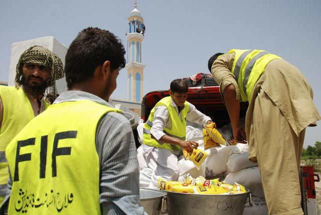 Volunteers of Falah-e-Insaniat Foundation (FIF), a welfare organization, arrange food packs before distributing them to people fleeing from the military offensive against Pakistani militants in North Waziristan, at a distribution point for internally displaced persons (IDP) in Nurar village, on the outskirts of Bannu, located in Pakistan's Khyber-Pakhtunkhwa province July 6, 2014.  REUTERS/Khuram Parvez