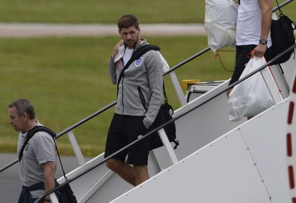 England's Steven Gerrard (C) arrives back from the 2014 World Cup in Brazil at Manchester airport, northern England June 25, 2014. REUTERS/Nigel Roddis