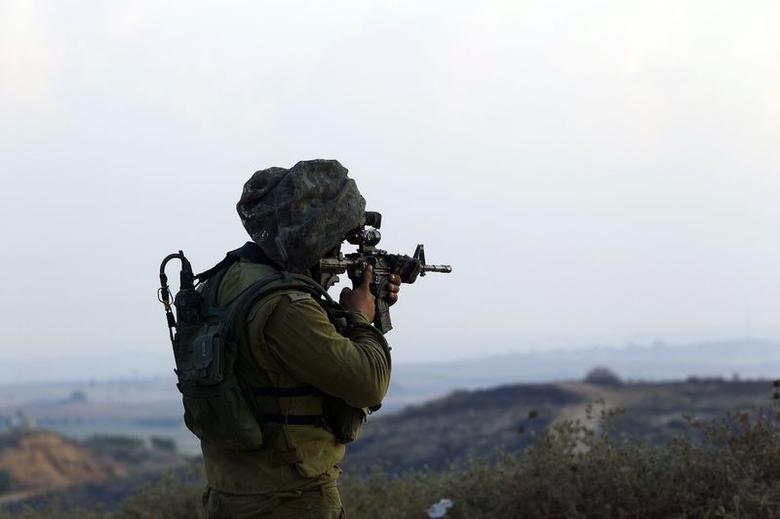 Israeli soldier holds up his weapon outside the northern Gaza Strip, near the site where Palestinian militants crossed the border from Gaza July 21, 2014. REUTERS/Ronen Zvulun
