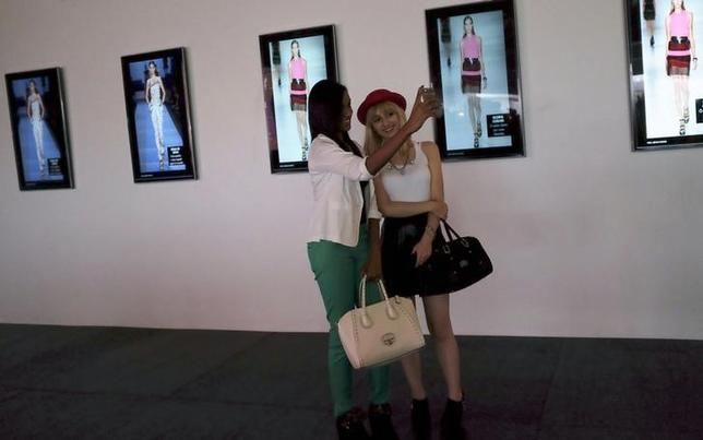 Visitors take a ''selfie'' with a mobile phone in front of a slideshow of the Agua de Coco Summer 2015 collection at Sao Paulo Fashion Week in Sao Paulo April 3, 2014. REUTERS/Nacho Doce/Files