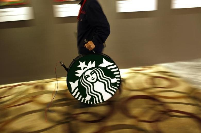 A man carries a Starbucks logo sign after a corporate event at a hotel in Shanghai April 19, 2012.   REUTERS/Carlos Barria