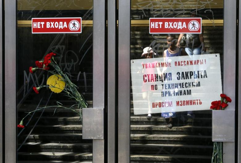 Flowers in memory of victims of Tuesday's accident, in which three carriages derailed on a train during morning rush hour, are left next to a sign informing passengers that the station is closed due to technical reasons, at the entrance to a metro station in Moscow July 16, 2014. REUTERS/Sergei Karpukhin