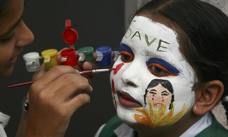 A girl gets her face painted with an awareness message on female foeticide during a face-painting competition in the northern Indian city of Chandigarh August 1, 2009. REUTERS/Ajay Verma