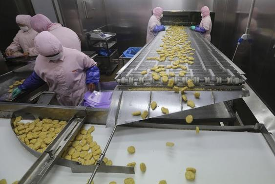 Employees work at a production line prior to a seizure conducted by officers from the Shanghai Food and Drug Administration, at the Husi Food factory in Shanghai, July 20, 2014. REUTERS-Stringer