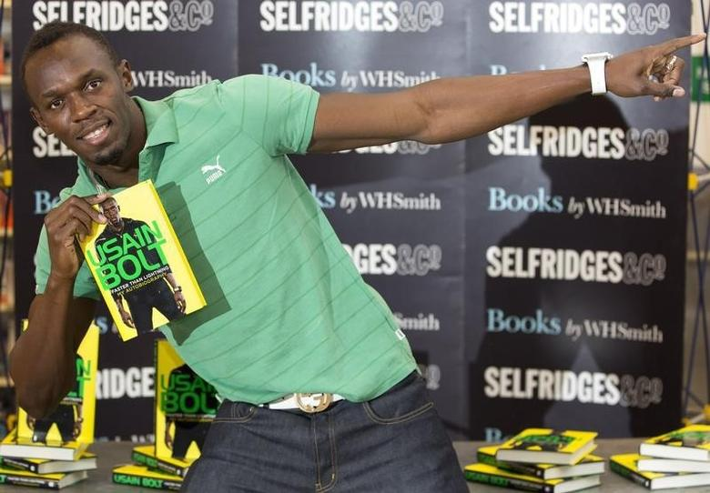 Jamaican athlete Usain Bolt poses for photographers with a copy of his autobiography, ''Faster than Lightning,''  at Selfridges in central London September 19, 2013. REUTERS/Neil Hall