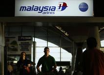 Un grupo de personas pasan junto al mostrador de  Malaysia Airlines en el aeropuerto internacional de Kuala Lumpur en Sepang, jul 18 2014. Un plan para reestructurar Malaysia Airlines podría ser anunciado a fines de agosto, dijeron dos fuentes con conocimiento del tema, después de que uno de sus aviones se estrellara la semana pasada en el este de Ucrania, el segundo desastre en impactar a la compañía este año.  REUTERS/Edgar Su