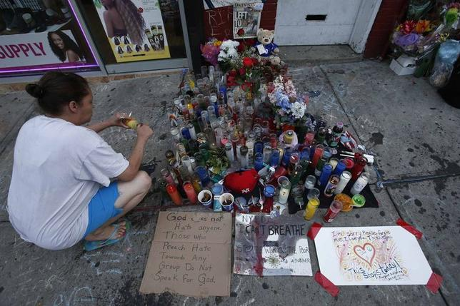 A woman pays respect with a candle at the memorial of Eric Garner in Staten Island, New York, July 21, 2014.  REUTERS/Eduardo Munoz