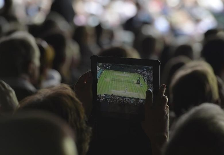 A spectator takes a photograph on an iPad during the men's singles final tennis match between Novak Djokovic of Serbia and Roger Federer of Switzerland at the Wimbledon Tennis Championships, in London July 6, 2014.  REUTERS/Toby Melville