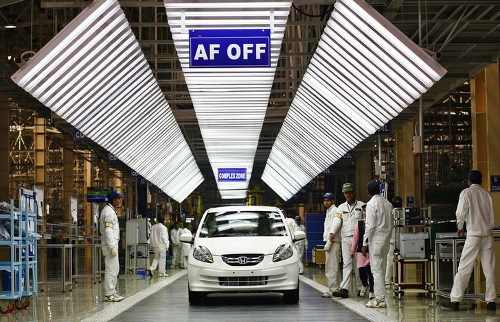Employees stand beside the Honda Amaze after giving it the final touches near the assembly line of the company's manufacturing plant in Tapukara, in Rajasthan, February 24, 2014.  REUTERS/Anindito Mukherjee/Files